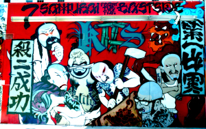 """7 Samurai from the Far Eastside"" rooftop mural for the DADA 1997 annual art show.  Mural features street artists SLICK, TEMPT, HYDE, RELIC, DUKE, PRIME, and SKEPT with calligraphic graffiti by Chaz Bojórquez. Photograph by Ben Higa"